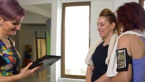 Persönlicher Trainer der Eignung, der Frau smartwatch überprüft, bevor Plan von Übungen auf Tabletten-PC erklärt wird stock video footage