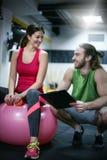 Persönlicher Trainer, der eine Trainingsberatung mit einem Kunden hat T stockbild