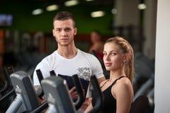 Persönlicher Trainer, der seinem weiblichen Kunden in der Turnhalle hilft stockfoto