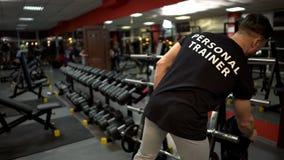 Persönlicher Trainer, der Trainingsstandort für seine Kundenturnhalle, Sportberuf vorbereitet stockfotografie