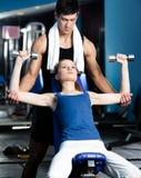 Persönlicher Trainer hilft Frau, mit Gewichten zu trainieren Stockfotografie