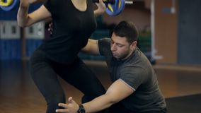 Persönlicher Trainer unterrichtet Mädchen, eine Übung mit Barbell auf ihren Schultern zu tun stock video