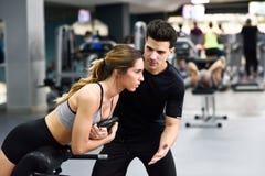 Persönlicher Trainer, welche junger Frau hilft, Gewichte anzuheben stockbilder
