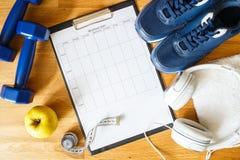 Persönlicher Trainingsplan mit Turnschuhen und Dummköpfen Stockfotos