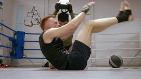 Persönliches Training des Boxers, adominal Übung mit seinem Trainer machend stock video