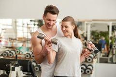 Pers?nlicher Trainer, welche einer jungen Frau hilft, Gewichte anzuheben lizenzfreies stockbild