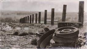 Perscective op een uitstekend landschap met oude banden en omheining stock afbeeldingen