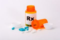 Perscription Pills. Two types of pills and perscription bottles with blue and white pills spilled out Royalty Free Stock Photography