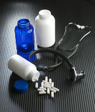 Perscriptions. Stethoscope and prescription bottles and capsules on black surface Royalty Free Stock Images