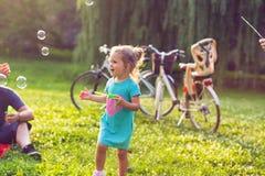A perseguição alegre da menina do tempo da família borbulha na natureza fotos de stock royalty free
