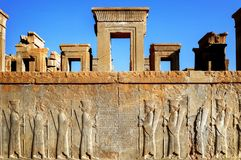 Persepolis is the capital of the ancient Achaemenid kingdom. sight of Iran. Ancient Persia. Bas-relief carved on the walls of old. Buildings against the blue Stock Photography