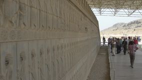 Persepolis relief wall. PERSEPOLIS, IRAN - MAY 3, 2015: Tourist taking photo of the relief on the wall in old city ruins, a capital of the Achaemenid Empire 550 stock video footage