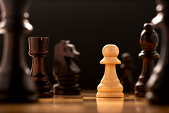 Perseverance in the face of a challenge. A conceptual image of a lonely light coloured wooden pawn standing on a chessboard surrounded by all the black chess Stock Image