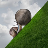 Perseverance. Symbol and sisyphus symbol as a determined snail pushing a boulder up a grass mountain as a metaphor persistence and determination to succeed Royalty Free Stock Photo