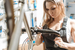 Persevering female mechanic repairing the bicycle in the garage. Full of concentration at work. Attentive observant pleasant mechanic standing in the garage and Stock Image