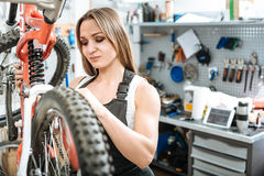 Persevering worker repairing the bicycle in the garage. Attentive to details. Interested athletic involved worker standing in the garage and working while Royalty Free Stock Image
