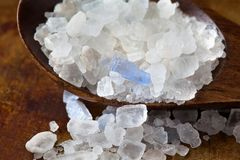 Persian blue salt crystal macro view. Mineral saline sodium chloride from Semnan Iran. Organic food condiment wooden Royalty Free Stock Image