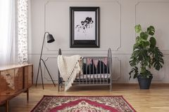 Persian carpet on the floor of mid century baby room interior with grey wooden crib, industrial black lamp and monster plant in. Pot royalty free stock images