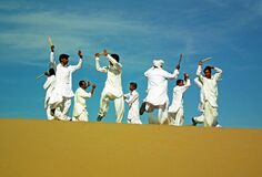 Persian folk dancers on sand dune in a festival in Eastern Iran