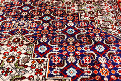 Persian Oriental Rug_close up view. Section of Persian oriental rug on wooden floor Royalty Free Stock Photos