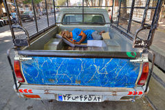 Persian worker sleeps in the back of a truck outdoors. Stock Photography
