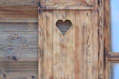 Persianas de ventana de una choza de madera con un agujero en forma de corazón Imagen de archivo libre de regalías