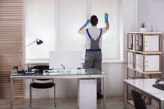 Persianas de ventana masculinas de la limpieza del trabajador con la esponja imagen de archivo libre de regalías
