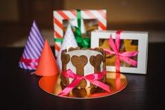 Persiga la torta y la galleta en cajas con el sombrero del cumpleaños Imágenes de archivo libres de regalías