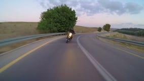 Persiga la vista de una motocicleta rápida que conduce en un camino curvado almacen de metraje de vídeo