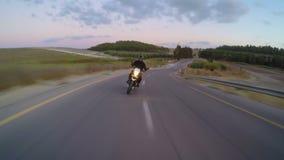 Persiga la vista de una motocicleta rápida que conduce en un camino curvado almacen de video