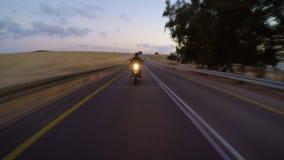Persiga la vista de una motocicleta rápida que conduce en un camino curvado metrajes