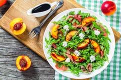 Persika-, arugula-, prosciutto- och getostsallad med balsamic Arkivbild