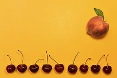 Persika och söt körsbär på guling arkivbilder