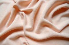 Persikabakgrund, mjuk torkduk, mjuk ärmlös tröja Arkivbild