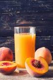 Persikafruktsaft i exponeringsglas Arkivbild