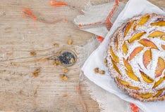 Persikapaj med sockerpulver över en linnetabelltorkduk Royaltyfria Bilder