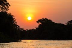 Persikasolnedgång över den brasilianska Pantanal och Cuiaba floden Arkivbild
