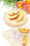 Persikasouffle i exponeringsglas och frukt i bakgrunden, närbild Arkivfoto