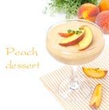 Persikasouffle i exponeringsglas och frukt i bakgrunden som isoleras Arkivfoto