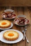 Persikatarts och koppar av svart te på träbakgrund Royaltyfri Foto