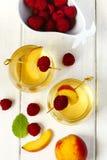 Persikavin och frukter på den vita trätabellen Arkivfoto