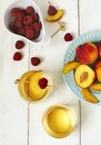 Persikavin och frukter på den vita trätabellen Arkivbild