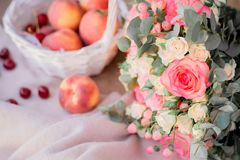 Persikor i den vita korg- och rosbuketten fotografering för bildbyråer