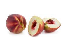persikor Mogna nya persikor med halvan och skivan som isoleras på whit Fotografering för Bildbyråer