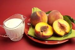 Persikor och det kräm- hybegreppet med pläterar av nya gula persikor Arkivfoto