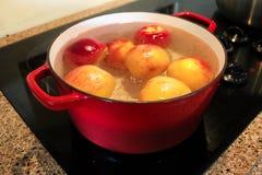 Persikor som kokas i en kruka så hudarna, kan tas bort Arkivbild