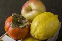 Persimmon και λεμόνι της Apple στον πίνακα Στοκ εικόνες με δικαίωμα ελεύθερης χρήσης