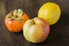 Persimmon και λεμόνι της Apple στον πίνακα Στοκ Εικόνες