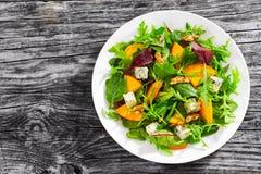 Persimmon σαλάτα με τα φύλλα μαρουλιού, το μπλε τυρί και τα ξύλα καρυδιάς Στοκ Φωτογραφίες