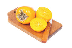 Persimmon σύνολο καρπού και τεμαχισμένος στο τέμνον χαρτόνι που απομονώνεται στην άσπρη ανασκόπηση Στοκ Εικόνα